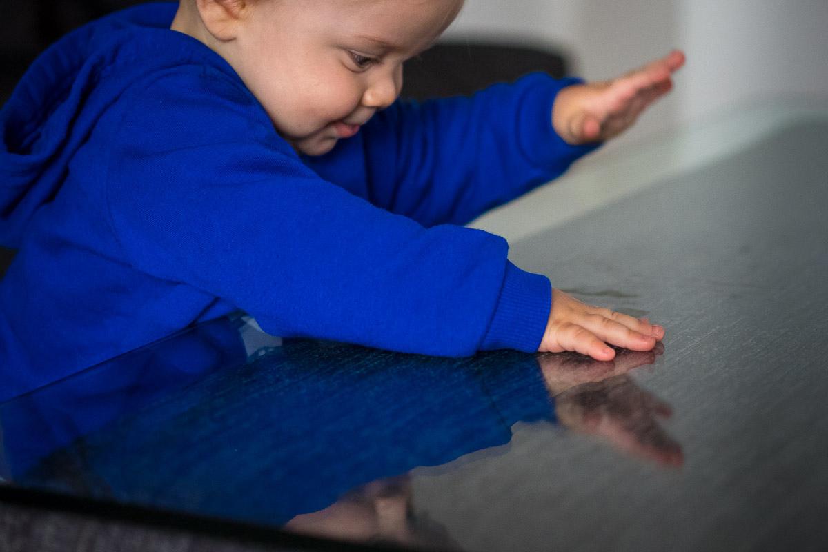 Kleinkind spielt an Wohnzimmertisch