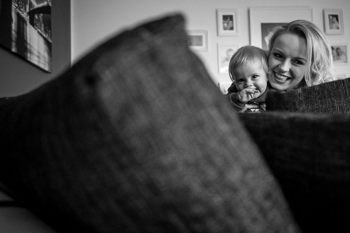 Mutter spielt mit Baby im Wohnzimmer als Familienfoto