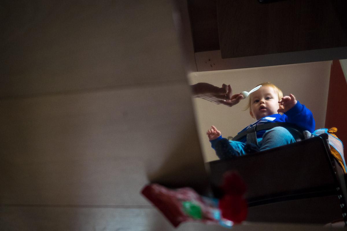 Natürliche Familienfotografie bei der Fütterung von Kind