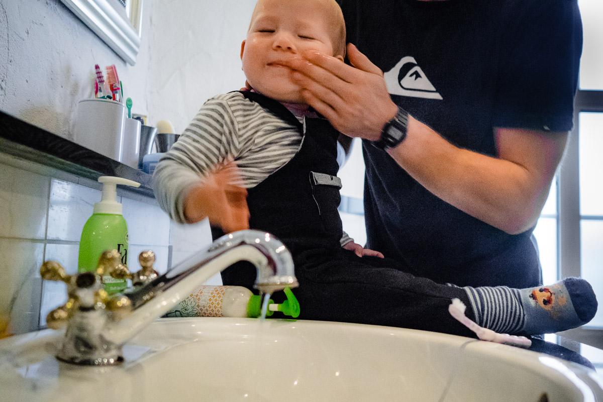 Vater waescht Babygesicht mit Babyfotograf Duesseldorf