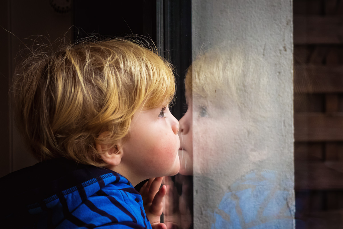Junge an Fensterscheibe mit Familienfotograf Wuppertal