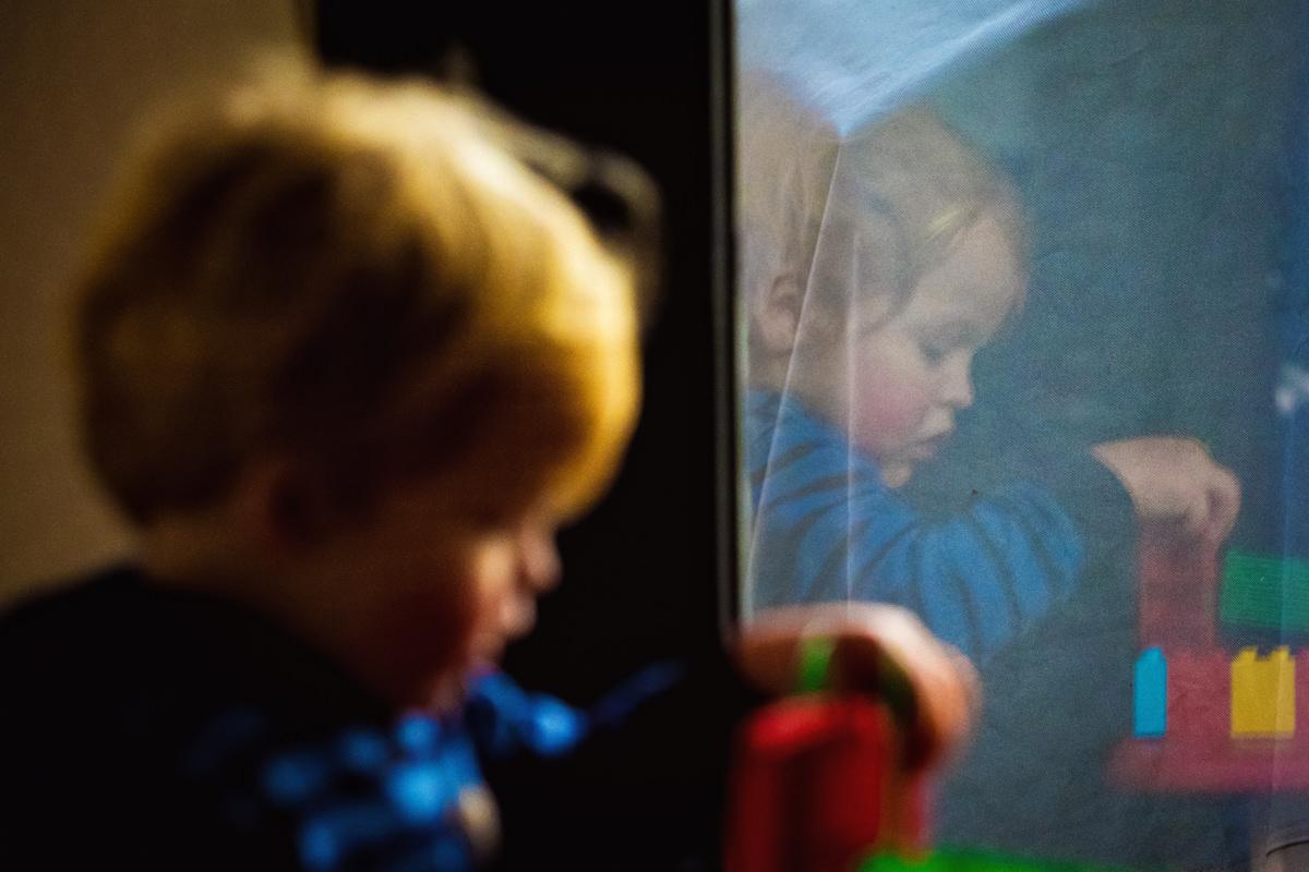Junge spiegelt sich im Fenster bei fotoshooting mit Kinderfotograf Wuppertal